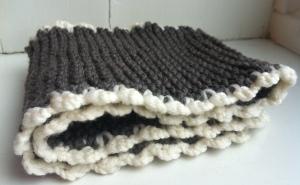 Babyskjerf strikket i brunt garn med naturhvit heklekant